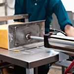 after-aging-the-pressed-blocks-are-moved-into-the-cutting-room-for-cutting-and-packaging-the-cheese-blocks-are-pushed-through-wire-cheese-cutters